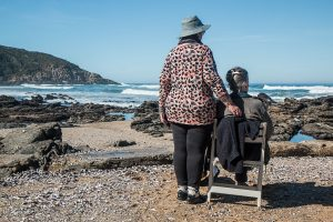 Two older women on a rocky meach staring out to sea