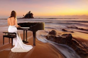 lady in white gown playing piano on a beach lookking at a sunset