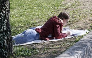 Teenage girl laying on a blanket writing in a notebook