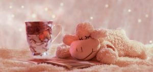 A cup of tea and a lamb stuffed animal