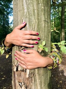 woman's arms hugging tree trunk