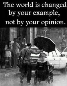 black and white photo with man holding an umbrella over lady in a wheel chair. Text overlay - The world is changed by your example, not by your opinion.