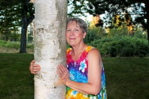 Gloria hugging a tree with a smile on her face