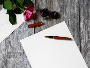 Pen and blank paper on a wooden table