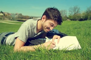 young man laying on stomach on the grass writing a letter