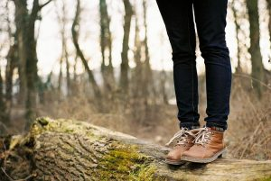 The legs of a woman in hiking boots standing on a log in a fall forest