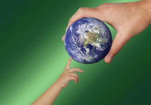 A child's hand reaching up to an adult hand holding a small globe