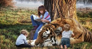 Older girl leaning against a tree reading a book, and two young boys playing with a sleeping tiger