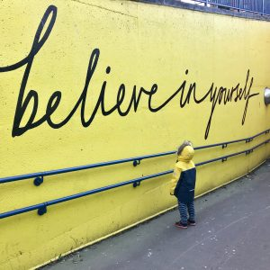 """Big letters written on a wall """"Believe in yourself"""" and a child looking up at the writing"""