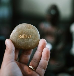 someone holding a rock with the word believe