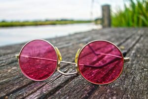 a pair of rose colored sunglasses laying on a dock