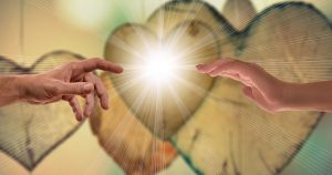 2 hands reaching toward a glowing heart in the centre