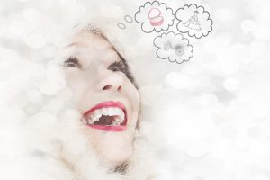 Image of a a women's smiling face with thought bubbles above her head.