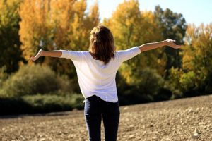 woman standing in a meadow with her arms outstretched