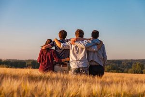 four teenage friends with arms around each other, sitting in a wheat field