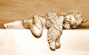 A cherub figurine lieing down with wings draped over the edge of a ledge