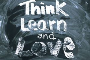 """A chalk board with words """"Think Learn and Love"""""""