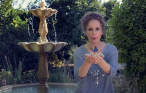 Lady in blue dress holding a blue butterfly, standing beside a concrete fountain