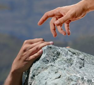 close up of a hand reaching for another hand to help them up a rock