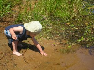 image of little boy playing in the mud